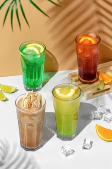 Beautiful still life composition with four transparent glasses of summer drink. green lemonade with lime, mint, lemon and citrus on a tropical background with shadows of a palm tree