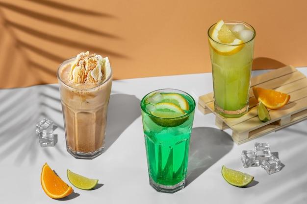 夏の飲み物の3つの透明なグラスと美しい静物画。ヤシの木の影と熱帯の背景にライム、ミント、レモン、柑橘類と緑のレモネード