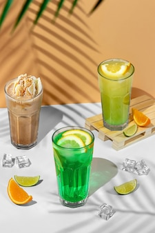 Beautiful still life composition with three transparent glasses of summer drink. green lemonade with lime, mint, lemon and citrus on a tropical background with shadows of a palm tree