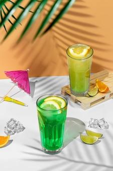 夏の飲み物の2つの透明なグラスと美しい静物画。ヤシの木の影と熱帯の背景にライム、ミント、レモン、柑橘類と緑のレモネード