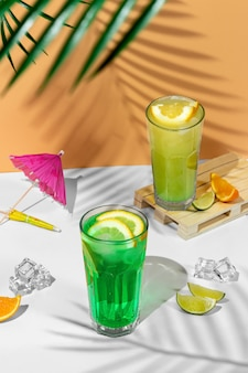 Beautiful still life composition with two transparent glasses of summer drink. green lemonade with lime, mint, lemon and citrus on a tropical background with shadows of a palm tree