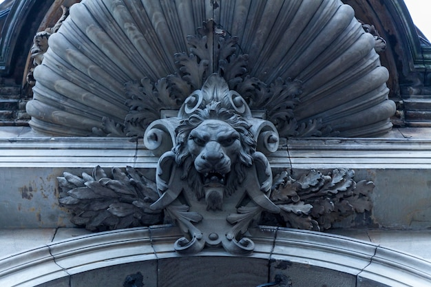 Beautiful stone decorations above the entrance door with the lion's head