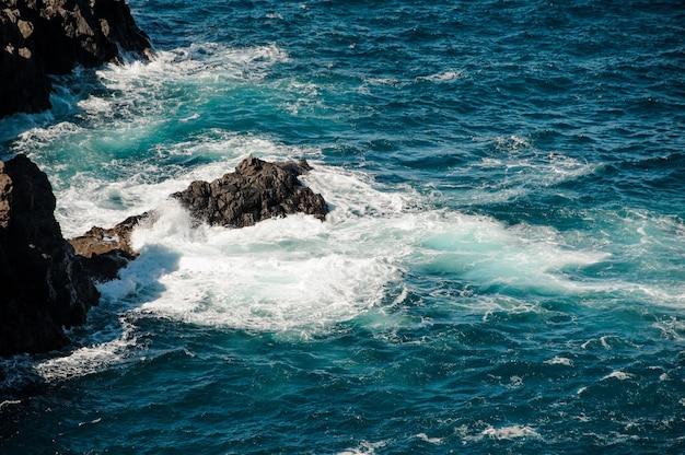 Красивое бурное глубокое море с белыми волнами и пеной вокруг скалы в солнечный день