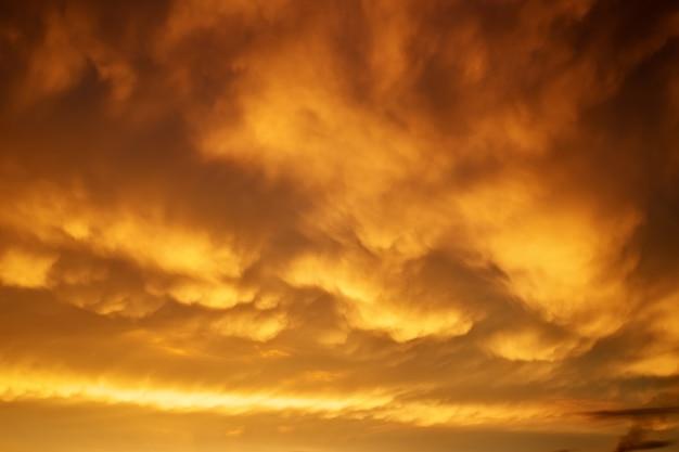 美しい嵐の夕焼け空。曇った抽象的な背景。夕焼けの色。