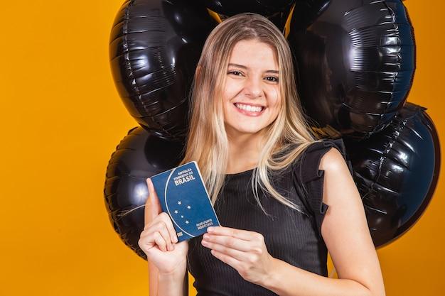 Красивая блондинка в путешествии. следующая поездка. девушка держит бразильский паспорт. на желтом фоне. черная пятница путешествия