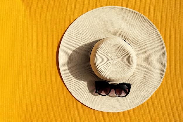 黄色い生き生きとした鮮やかな背景にサングラスを持つ美しい麦わら帽子。上面図。夏の旅行休暇の概念。