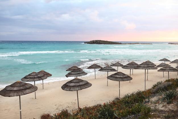 空のビーチ、明るい青い水と空、楽園の熱帯のビーチ、リラックスできる時間、素晴らしい景色、人なし、夕日を背景にビーチに美しい藁傘。セレクティブフォーカス