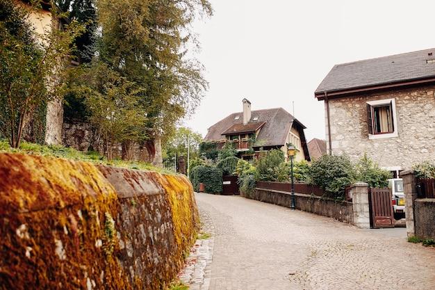 Красивая улица в анси с каменным забором со мхом, старинные постройки. фото высокого качества