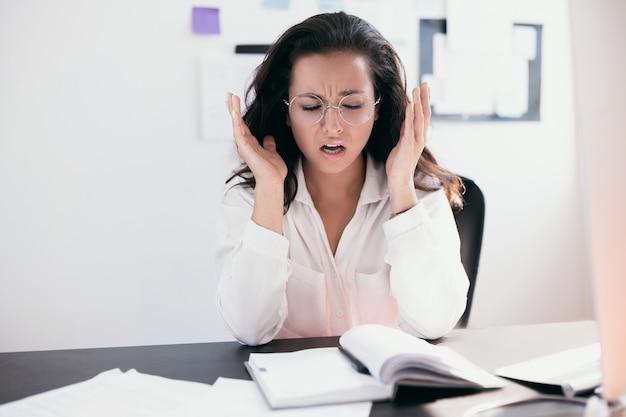 사무실에서 고통 때문에 머리를 들고 책상에 앉아 아름다운 스트레스 젊은 회사원
