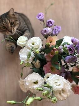 床やテーブルの上に花のガラスの花瓶と花で遊ぶ美しい縞模様の猫