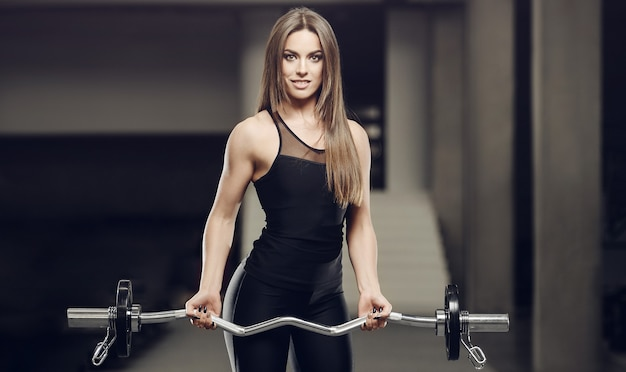 Beautiful strong athletic muscular young caucasian fitness girl workout training in the gym