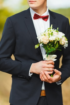 Beautiful strong groom in a suit with a tie, holding a bridal bouquet