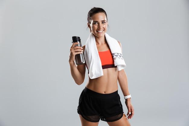 아름 다운 강한 행복 쾌활 한 젊은 스포츠 여자 목에 수건으로 고립 된 실내 식 수 포즈.