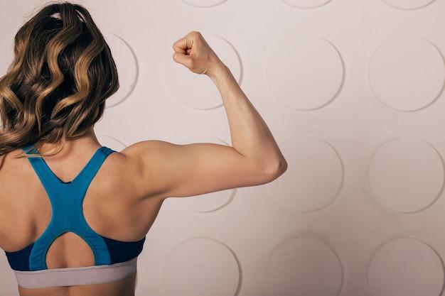 上腕二頭筋と腕の筋肉を曲げる美しい強い筋肉の女性。後ろから見たとき、彼女の引き裂かれた背中と腕を見せてください。