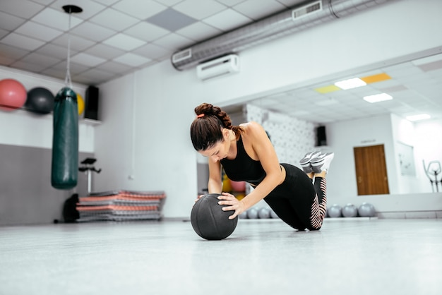 Beautiful strong woman doing push up on ball at the gym.