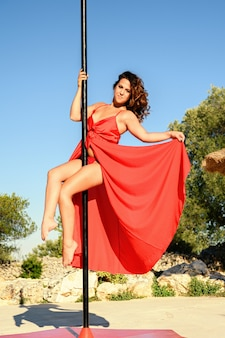 Beautiful strong woman making a pose on a pole wearing a long red dress.
