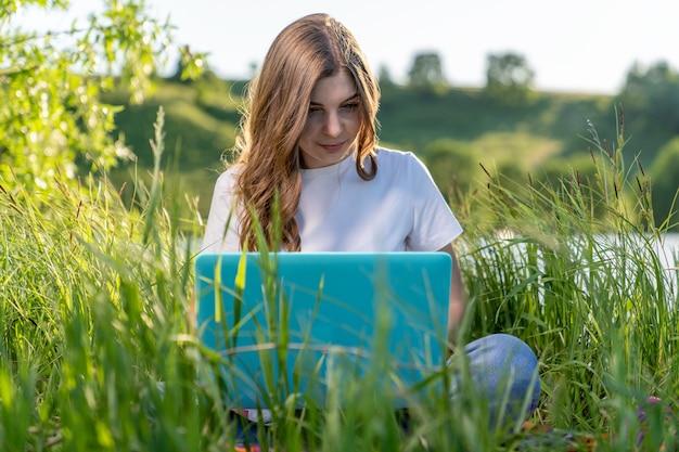 美しい学生の女の子は、ラップトップを膝の上に置いて湖のほとりの芝生に座って、熱心に何かを調べます