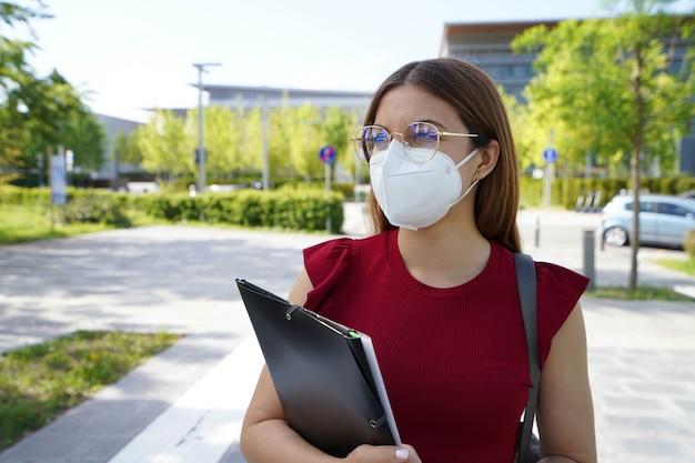 現代の通りを歩くffp2保護マスクを身に着けている美しい学生の女の子