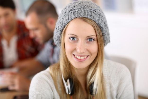 Beautiful student girl wearing hat in class