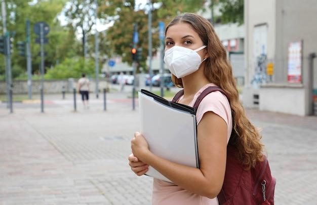 Красивая студентка с защитной маской возвращается в школу после пандемии коронавируса