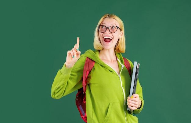 緑の壁にポーズをとる美しい学生。