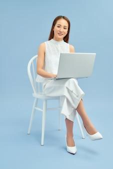 Красивый студент сидит в кресле с ноутбуком