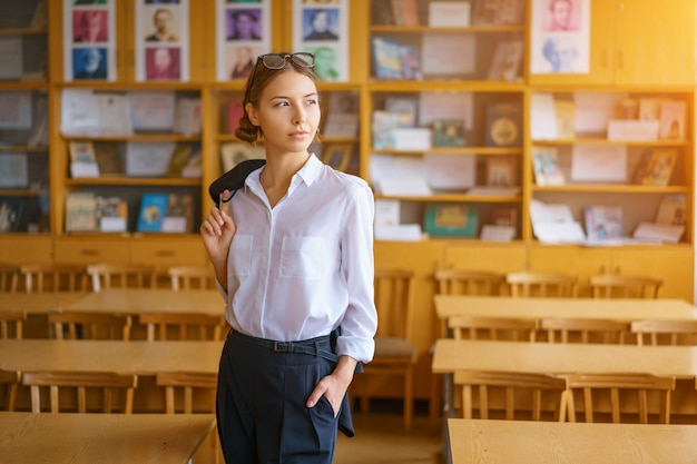 A beautiful student stands in the classroom