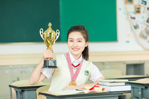 Beautiful students holding trophies