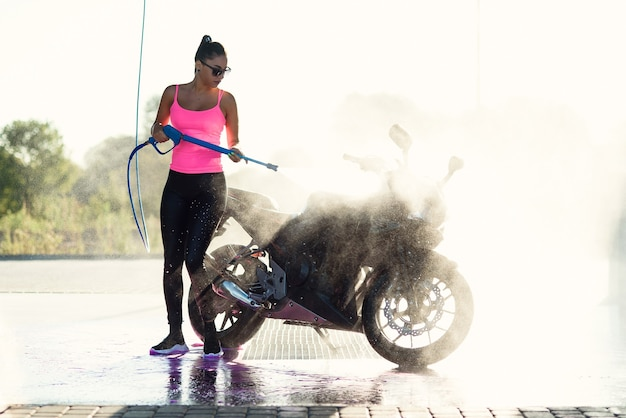 Beautiful stunning woman washes a motorcycle in self service carwash with high pressure water jet in morning at sunrise.
