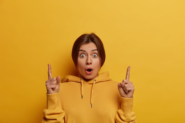 Beautiful stupefied european woman indicates upwards, introduces new product, gasps from wonder, has bugged eyes, invites to click promo banner, wears hoodie, isolated over yellow wall