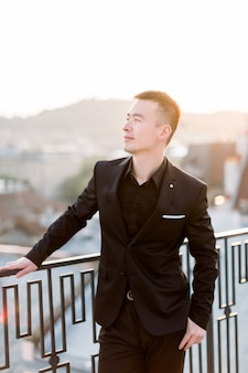 Beautiful stylish asian groom in black suit standing on the terrace of the building