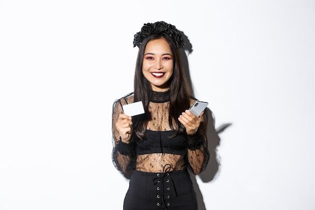 Bella donna asiatica alla moda in costume di halloween che tiene il telefono cellulare con carta di credito e sorridente, in piedi su sfondo bianco.