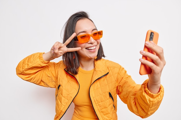Beautiful stylish asian woman takes selfie on mobile phone makes v sign smiles  has positive face wears orange sunglasses and jacket isolated over white wall. modern lifestyle