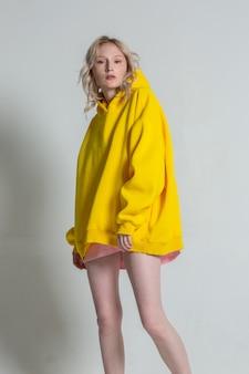 白い背景の上の素足でポーズをとって長い黄色のパーカーの美しいスタイリッシュなブロンドの女性