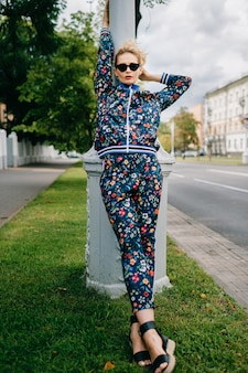 거리에서 포즈를 취하는 컬러 정장에 아름다운 세련된 금발 모델