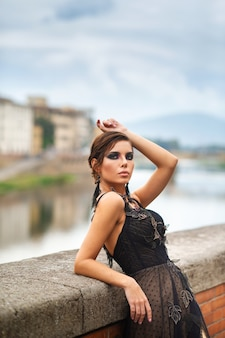 Beautiful stylish bride in a black dress stands on the embankment in florence, italy.