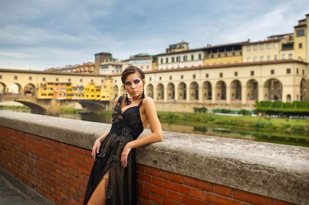 イタリア、フィレンツェの堤防に黒いドレスを着た美しいスタイリッシュな花嫁が立っています。