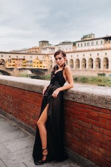 黒のドレスを着た美しいスタイリッシュな花嫁が、イタリアの旧市街にある黒のドレスを着たモデルであるフィレンツェを歩きます。