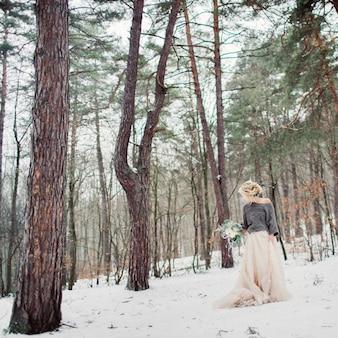 Bella sposa elegante a piedi nel parco invernale