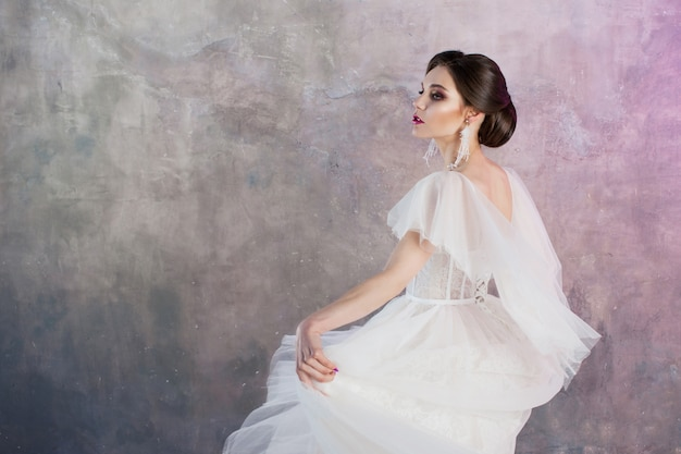 Beautiful and stylish bride in wedding dress with a lush flying skirt in