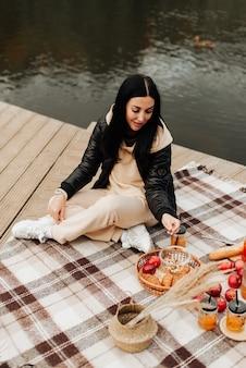 革のジャケットの美しいスタイリッシュなブルネットは、縞模様の格子縞の秋のピクニックに座っています
