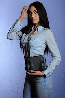 黒のクラッチを保持しているジーンズの美しいスタイリッシュなブルネット