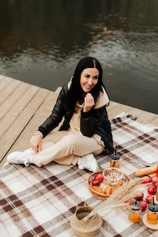 Beautiful stylish brunette in a leather jacket sits on a striped plaid autumn picnic