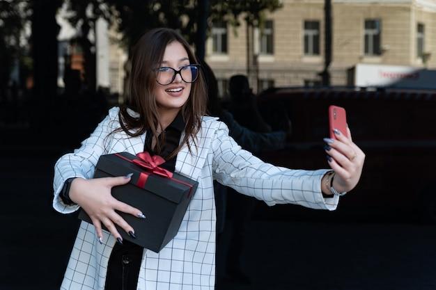 그녀의 손에 선물을 들고 있는 아름다운 세련된 브루네트는 스마트폰으로 셀카를 만듭니다.