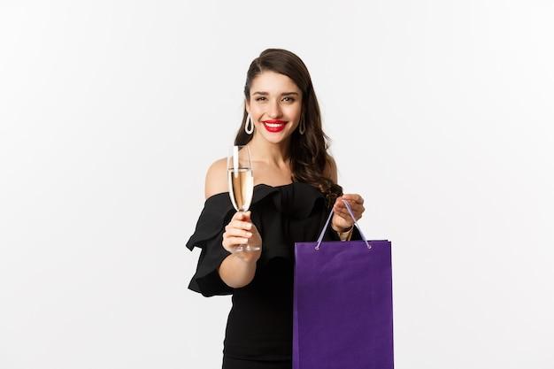 Bella ed elegante donna bruna che alza un bicchiere di champagne, festeggia il natale, tiene in mano la borsa della spesa con regali, in piedi su sfondo bianco