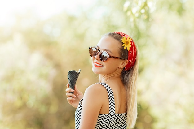Beautiful stylish caucasian girl in dark sunglasses holds black ice cream cone in her hands. fashionable young woman eats ice cream in park and smiles