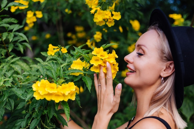 Beautiful stylish caucasian happy woman in black dress and classic hat in park surrounded by yellow thai flowers