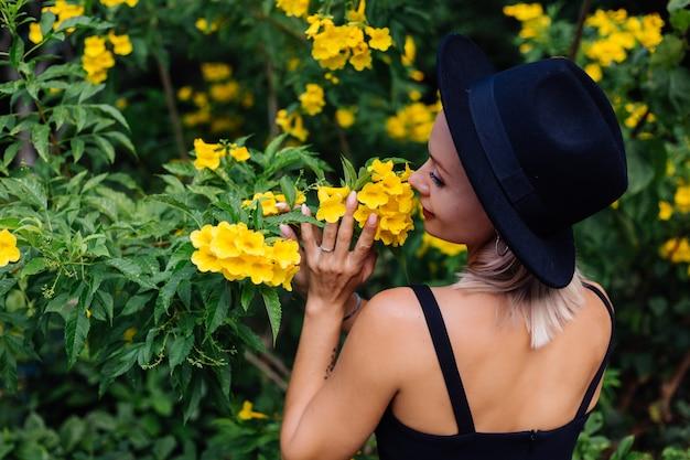 黄色のタイの花に囲まれた公園で黒のドレスと古典的な帽子の美しいスタイリッシュな白人の幸せな女性