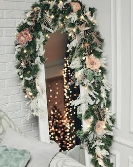 花とトウヒの枝で飾られた美しいスタイリッシュなクリスマスミラー