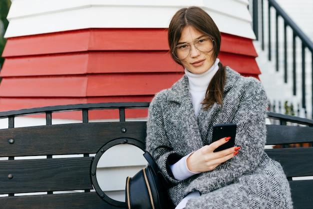 Красивая стильная городская девушка брюнетка в очках и сером пальто сидит на скамейке под открытым небом, держит смартфон и улыбается